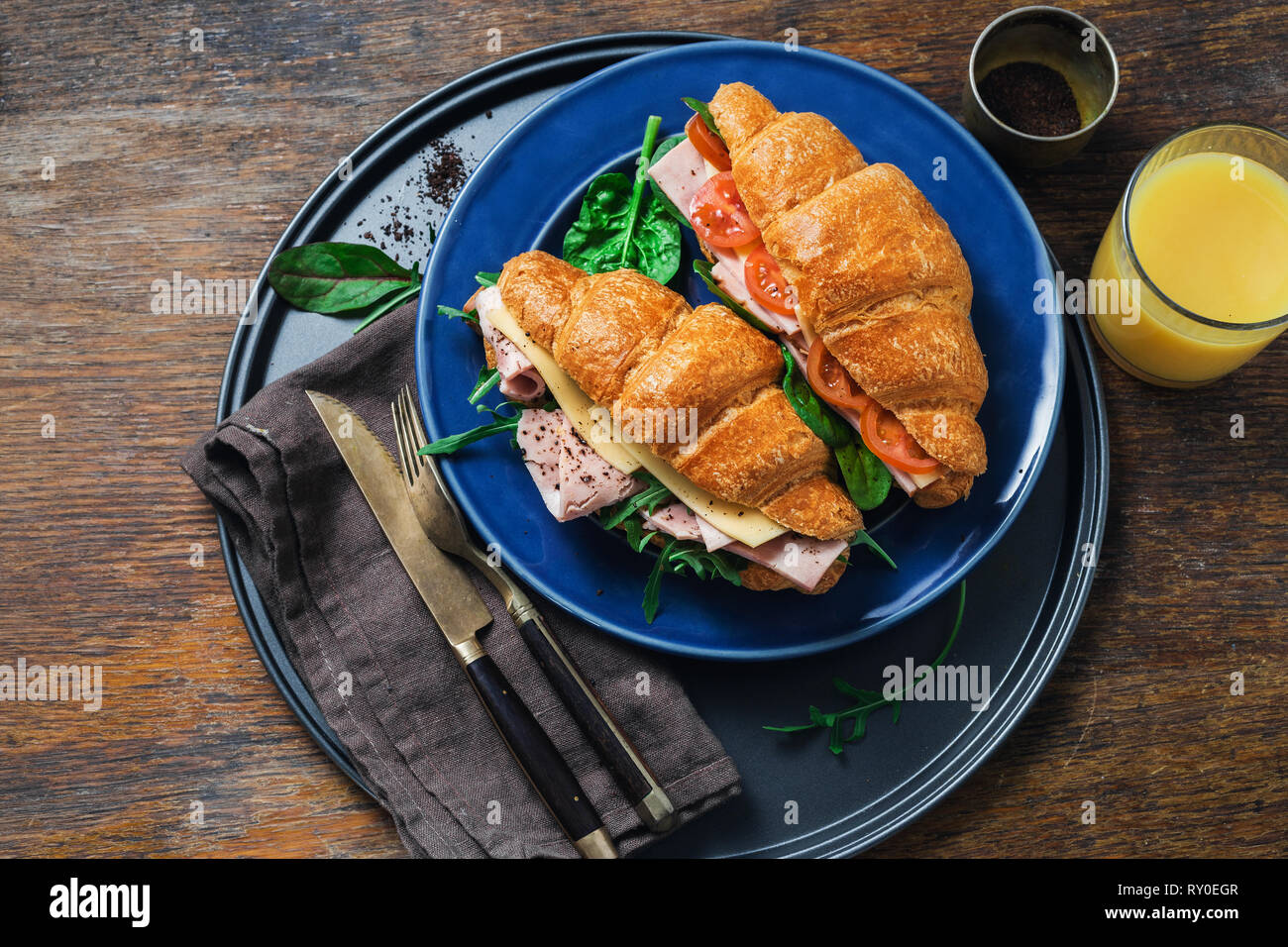 Fresh croissant sandwiches with orange juice on wooden table - Stock Image