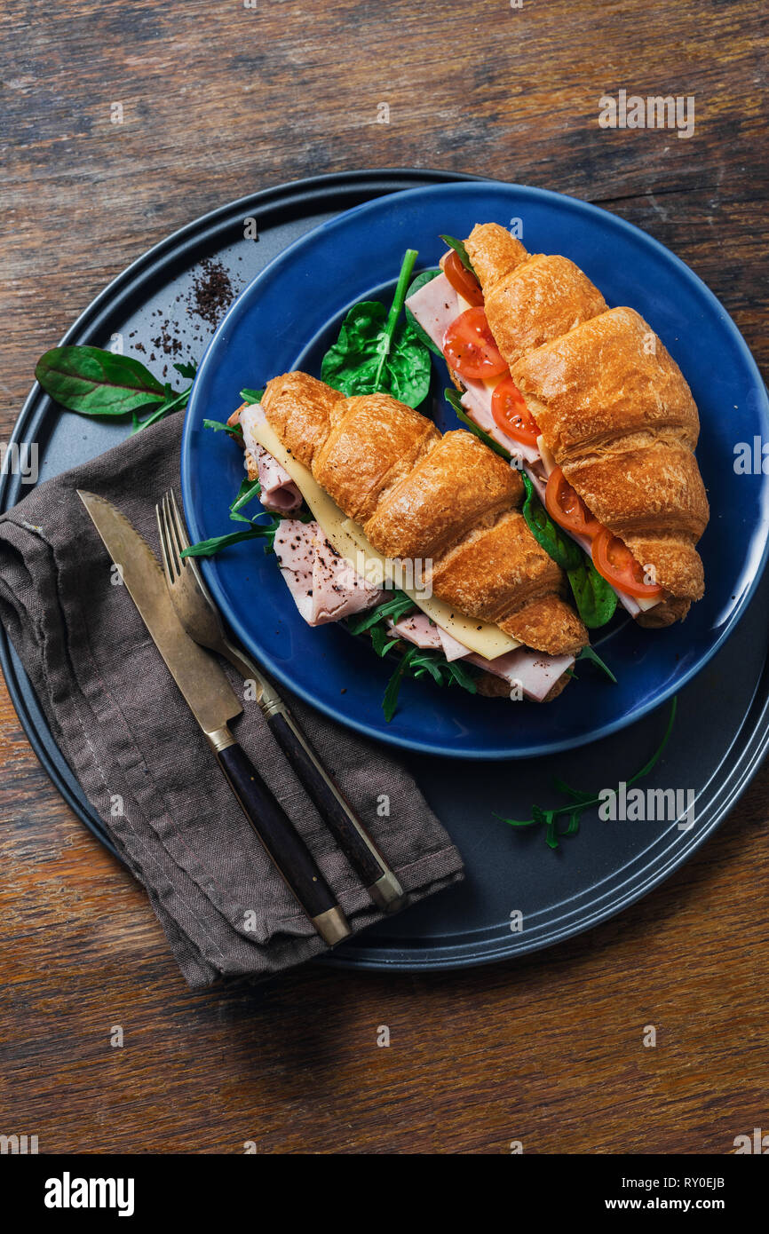 Breakfast croissant sandwiches served on blue plate on wooden table - Stock Image