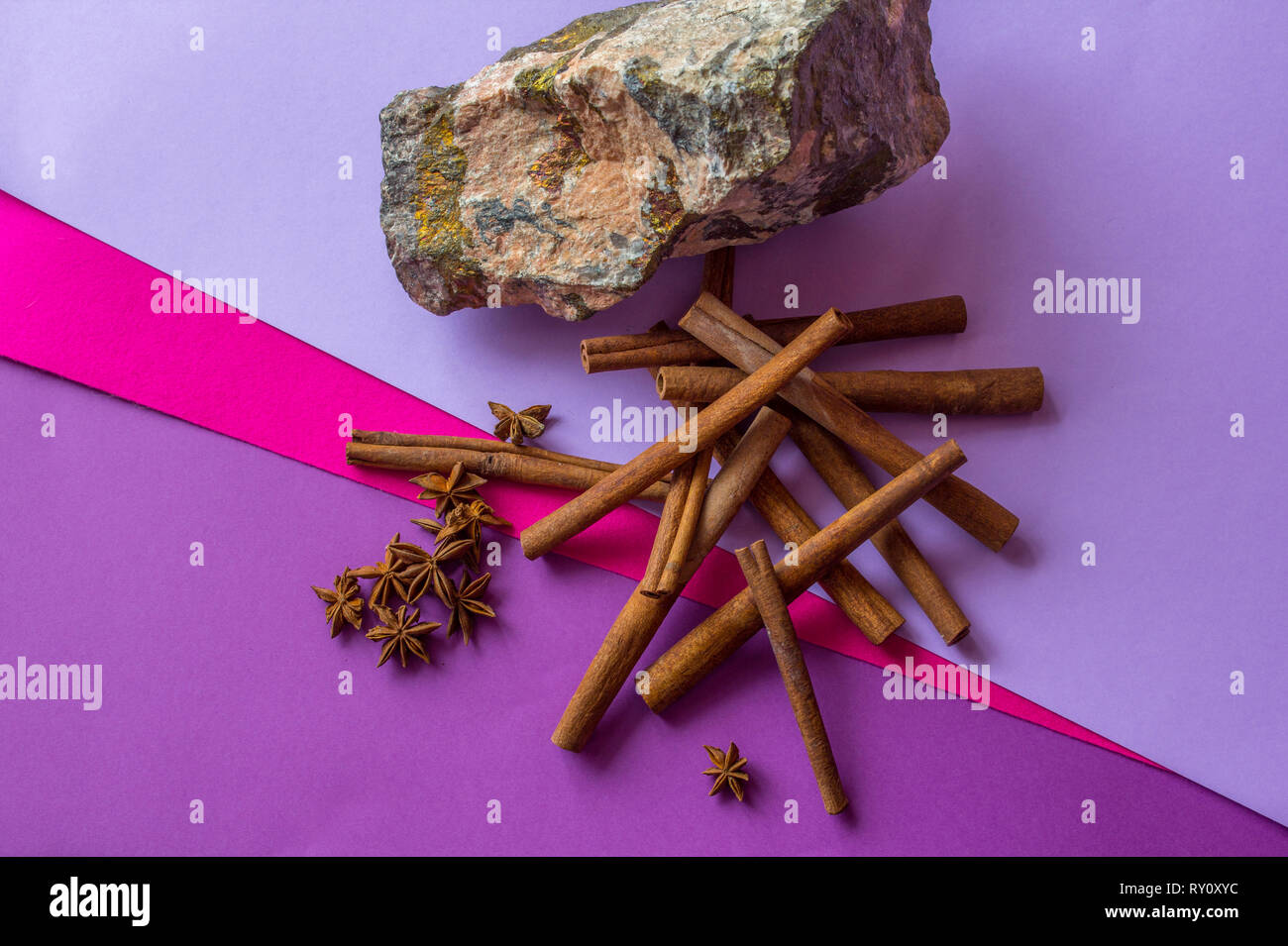 Still life of stone, cinnamon sticks and anise stars lying on coloured background - Stock Image