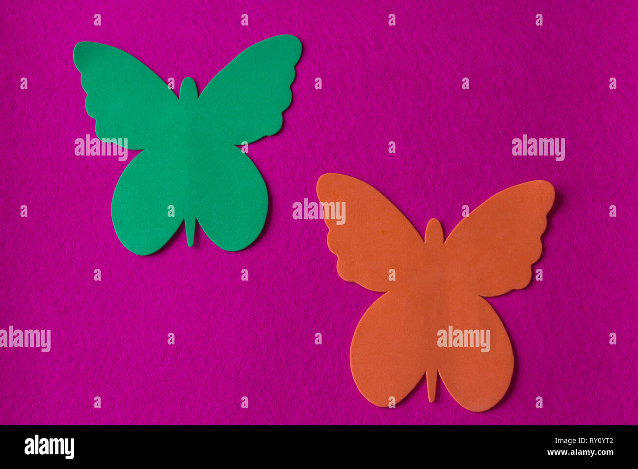 Green and orange butterflies made of soft material on a fuchsia rag background - Stock Image