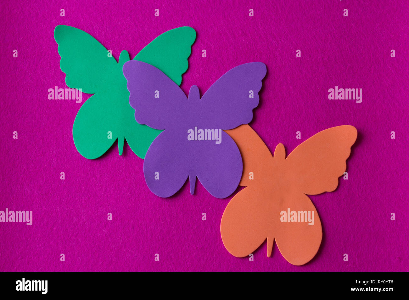 three bright and coloured butterflies made of soft material on a fuchsia rag background - Stock Image