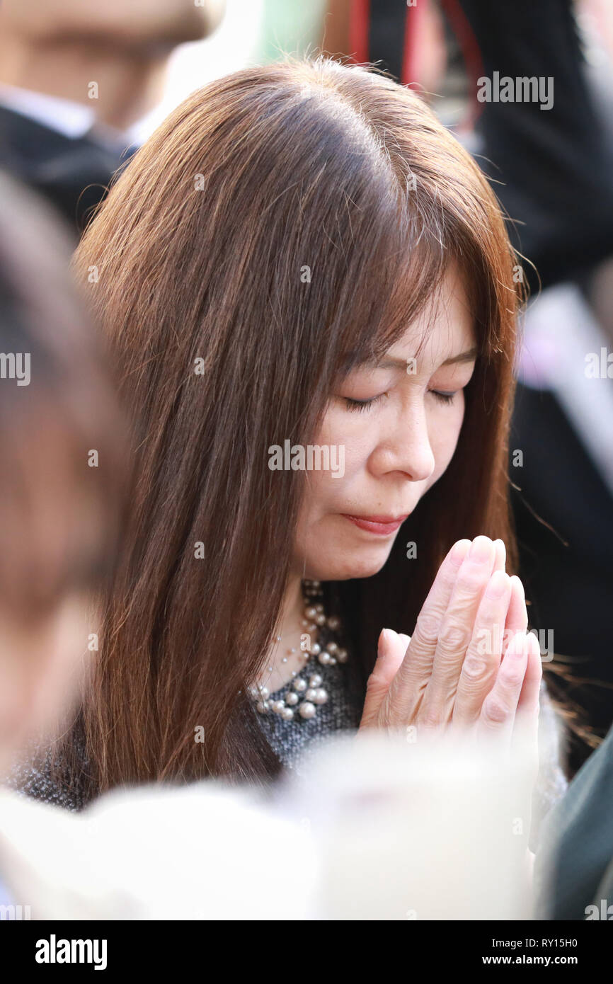 Tokyo, Japan. 11th Mar, 2019. A woman mourns for the victims of the March 11, 2011 earthquake-triggered tsunami during a memorial ceremony in Tokyo, Japan, March 11, 2019. Ceremonies were held across Japan on Monday to mark the eighth anniversary of a powerful earthquake-triggered tsunami, which obliterated swathes of the nation's northeastern seaboard and triggered the worst nuclear crisis since the 1986 Chernobyl disaster. A moment of silence was observed at a ceremony held in Tokyo and supported by the government. Credit: Du Xiaoyi/Xinhua/Alamy Live News - Stock Image