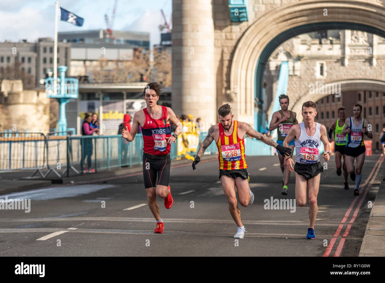 Maximilion Nicholls, Ash Harrell and Ross Skelton running in the Vitality Big Half half marathon crossing Tower Bridge, London UK. Strong wind blowing - Stock Image