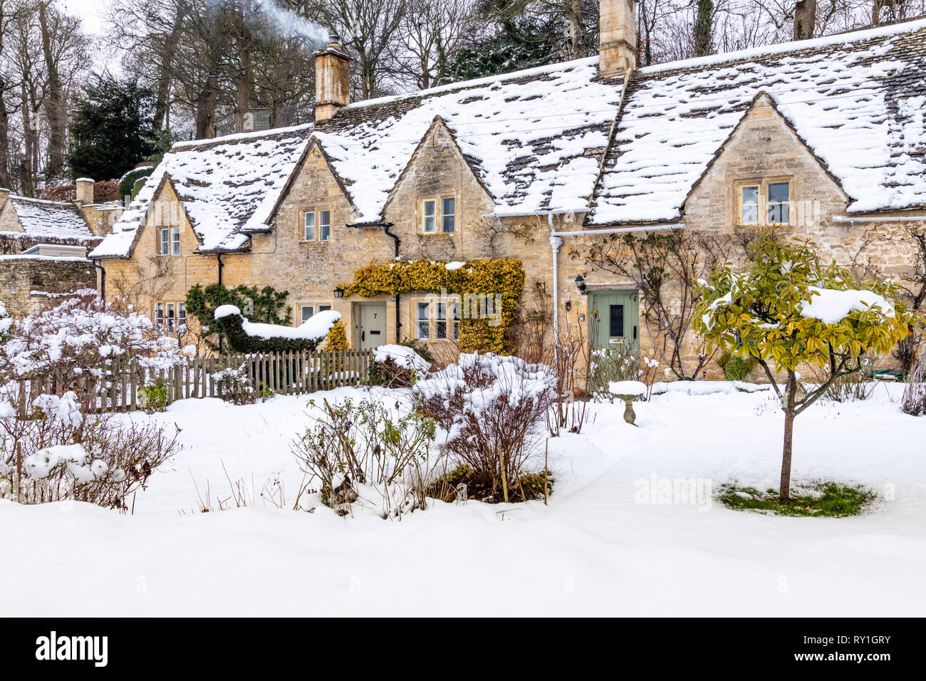 Cotswold stone cottages and gardens covered with snow at Bibury, Gloucestershire UK - Stock Image