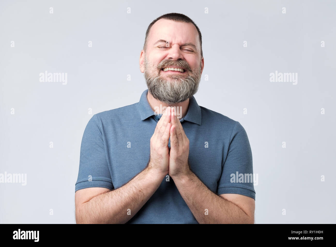 Mature bearded man join hands together begging asking for forgiveness help - Stock Image