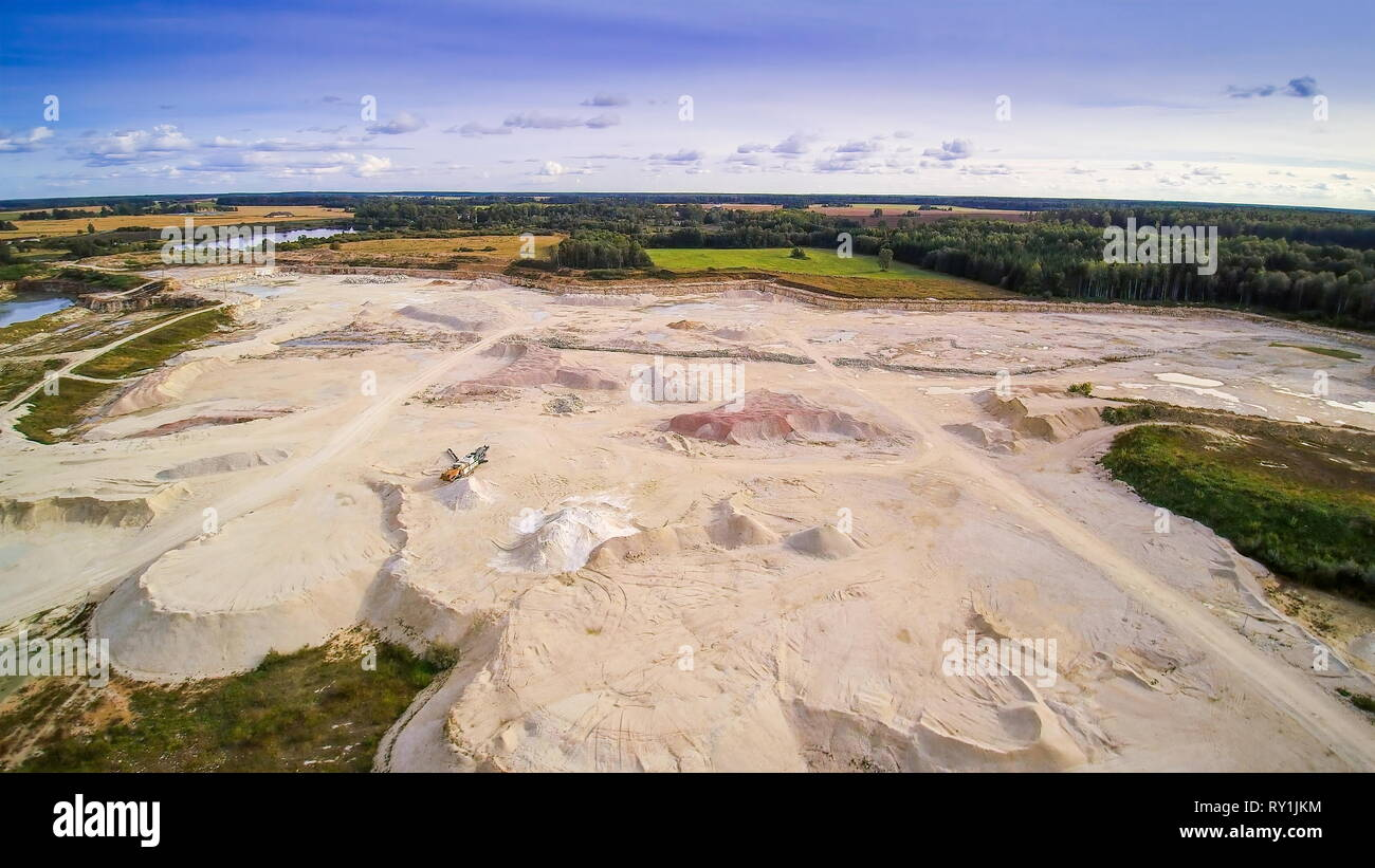 A limestone quarry area in the middle of the forest. Limestone is a sedimentary rock composed largely of the minerals calcite and aragonite - Stock Image