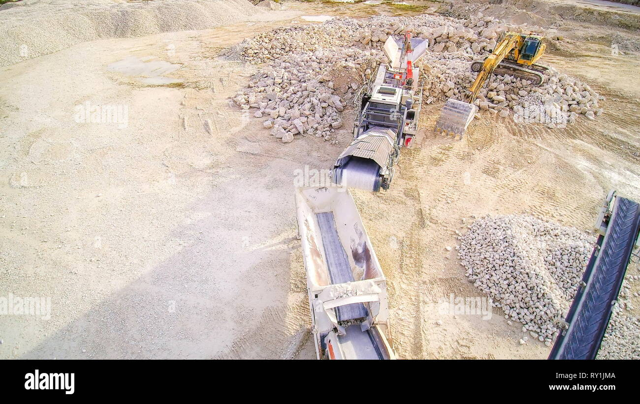 The big trucks and machineries in the quarry area. There are limestone crusher and the backhoe surrounded with big stones - Stock Image