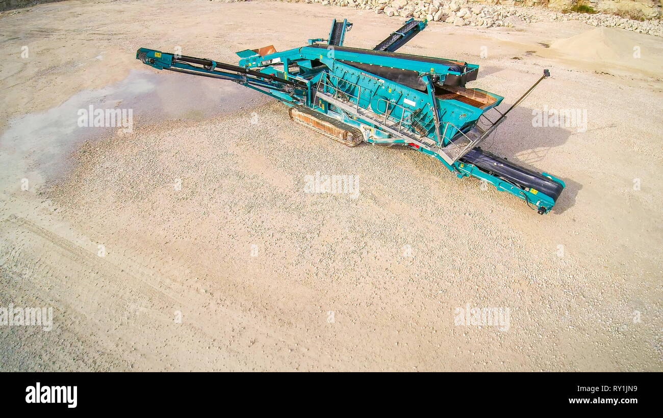 The green big limestone crusher machine that is in the middle of the quarry area - Stock Image
