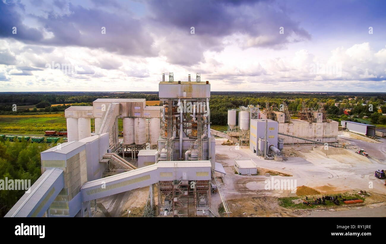 Overview of the limestone factory where there are lots of stones inside and some trucks and machineries moving inside - Stock Image