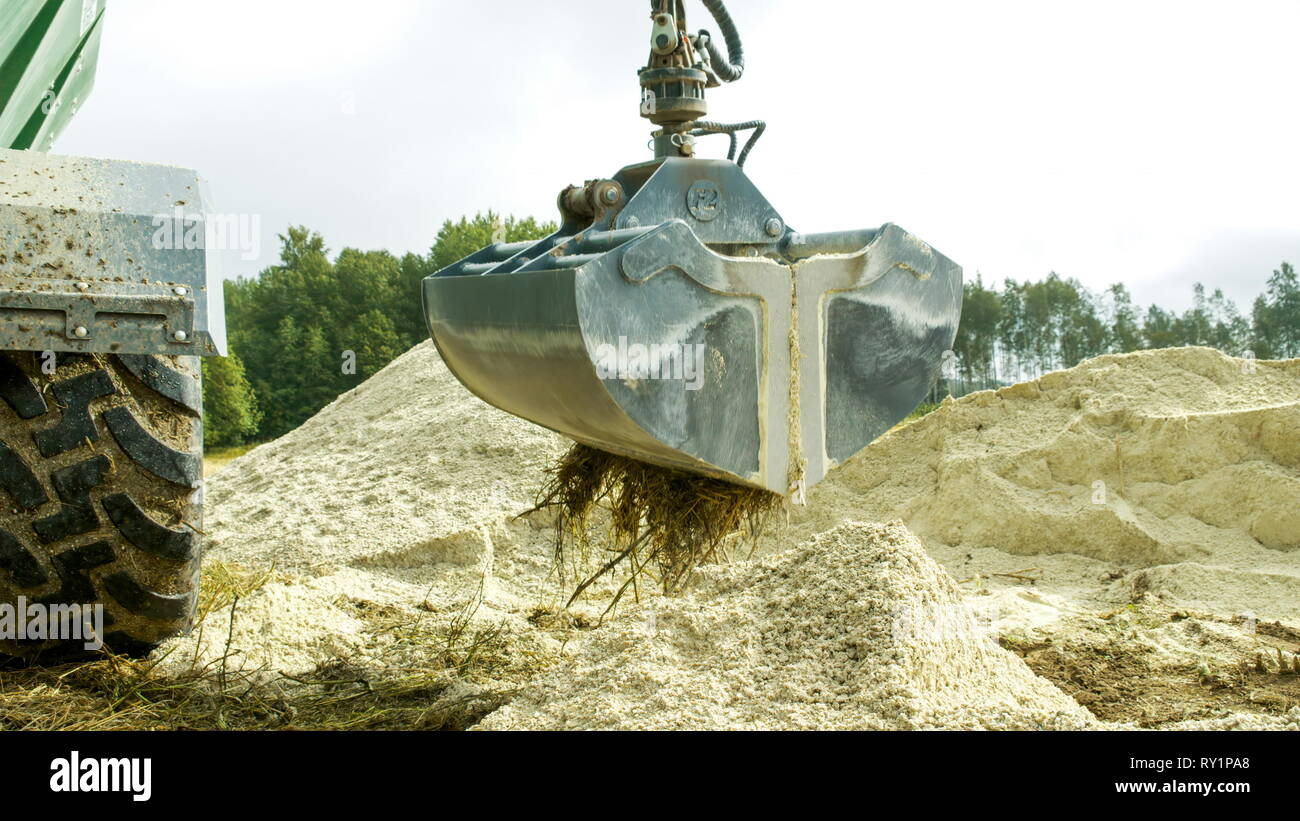 The big backhoe getting some powdered limestones on a mining site in a quarry - Stock Image
