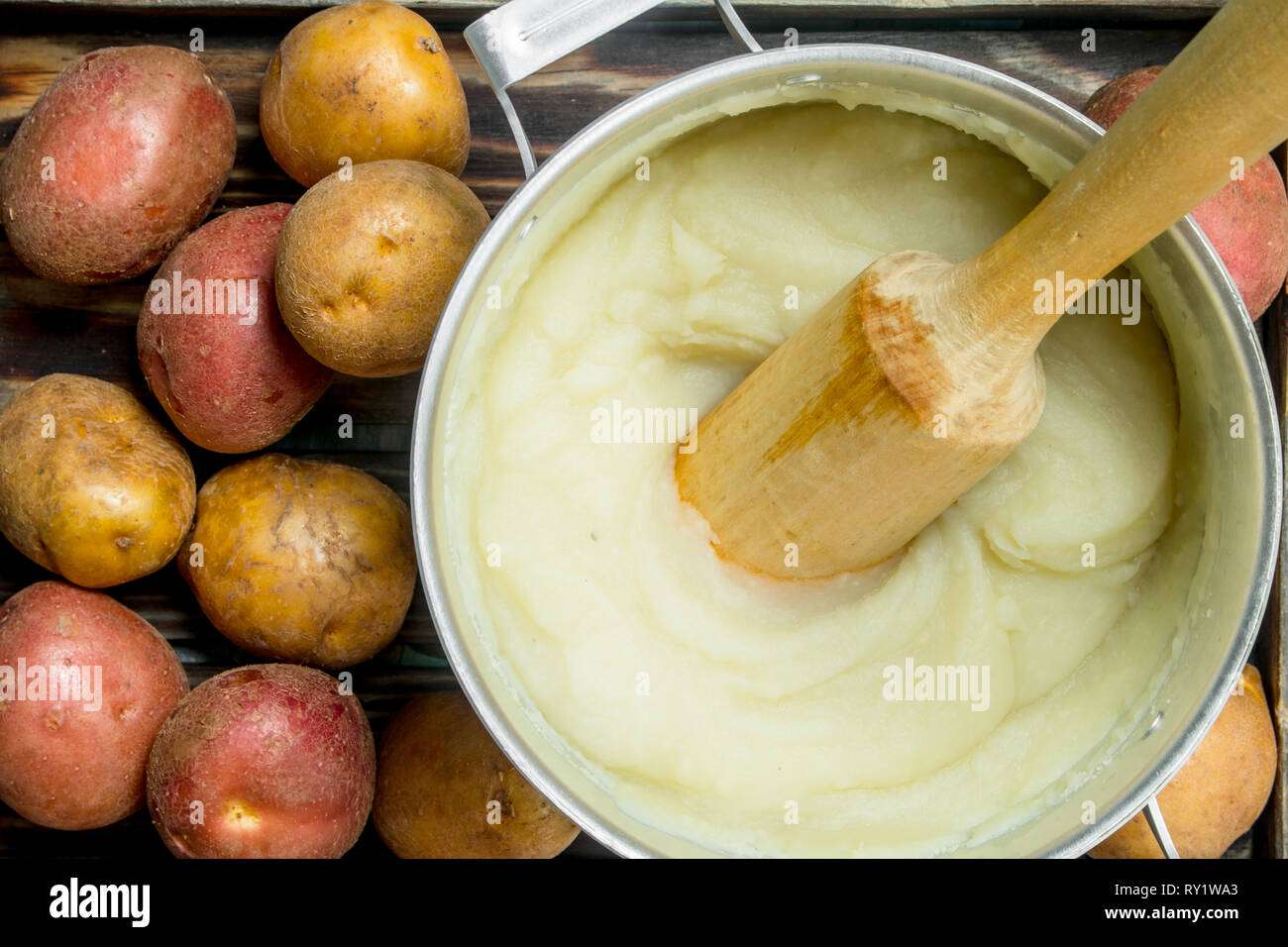 Mashed potatoes in a pot . On a rustic background. - Stock Image