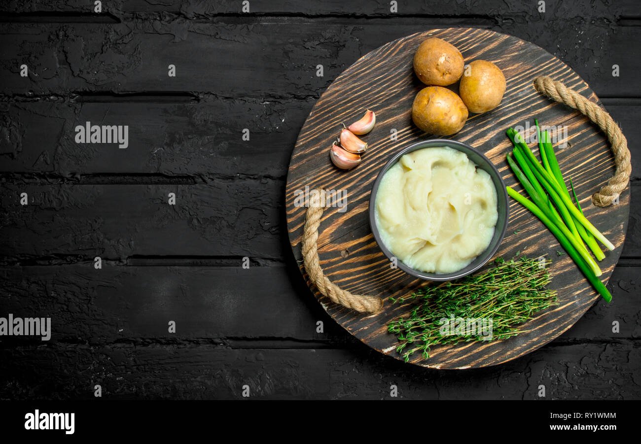Mashed potatoes in a bowl with herbs and garlic. On a rustic background. - Stock Image