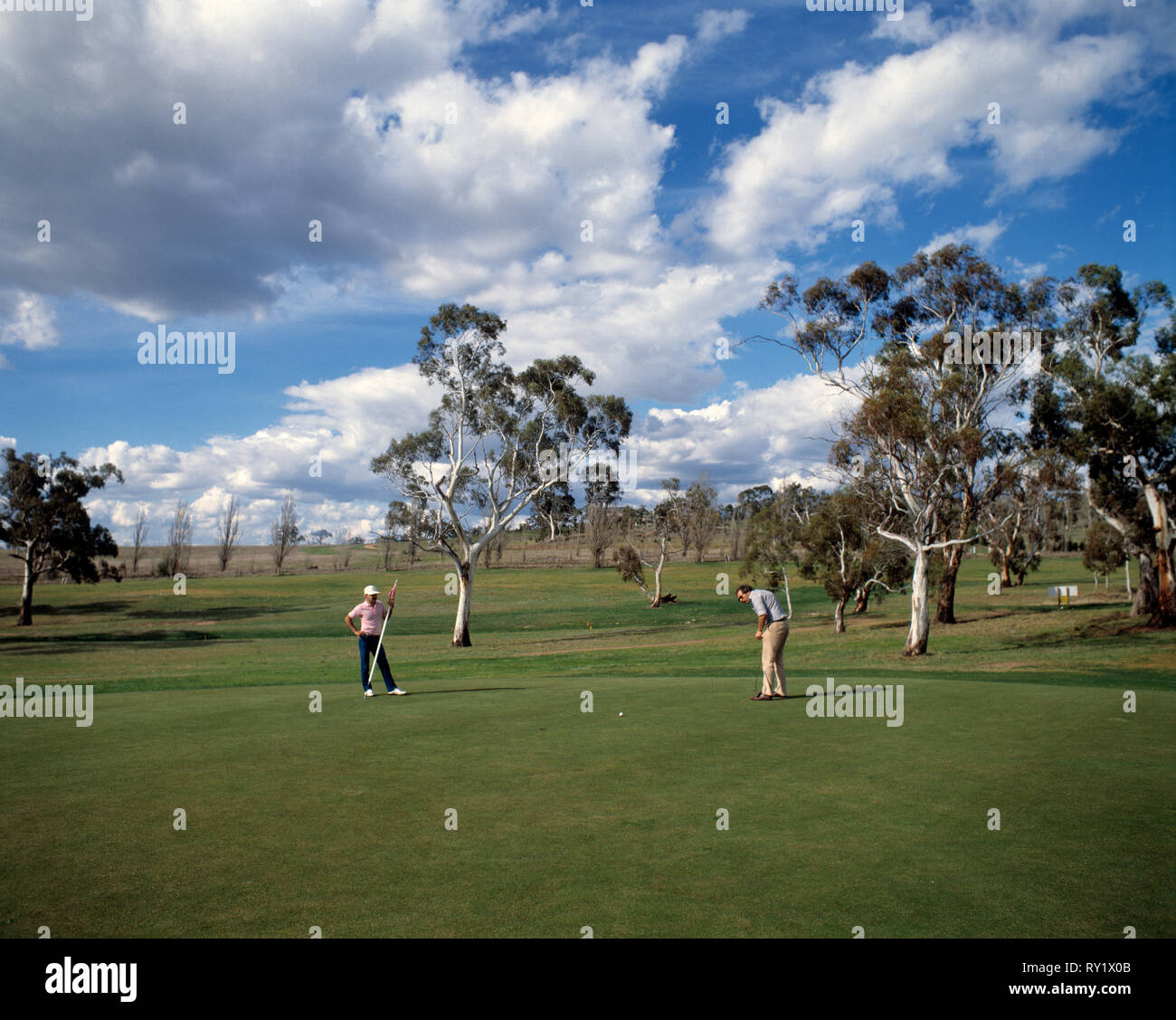 Australia. New South Wales. Snowy Mountains. Cooma golf course. Two men on putting green. - Stock Image