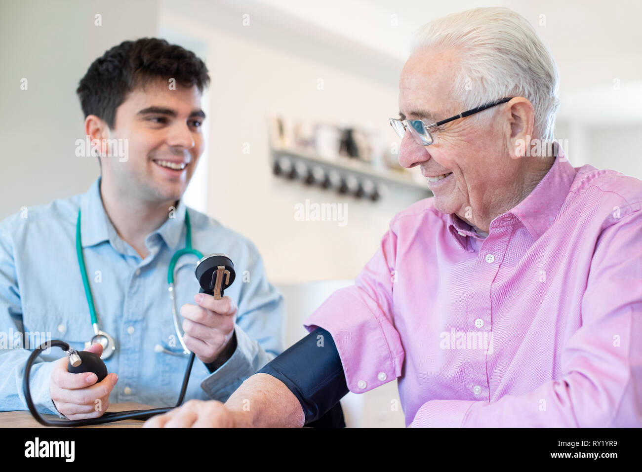 Male Doctor Measuring Blood Pressure Of Senior Man At Home - Stock Image