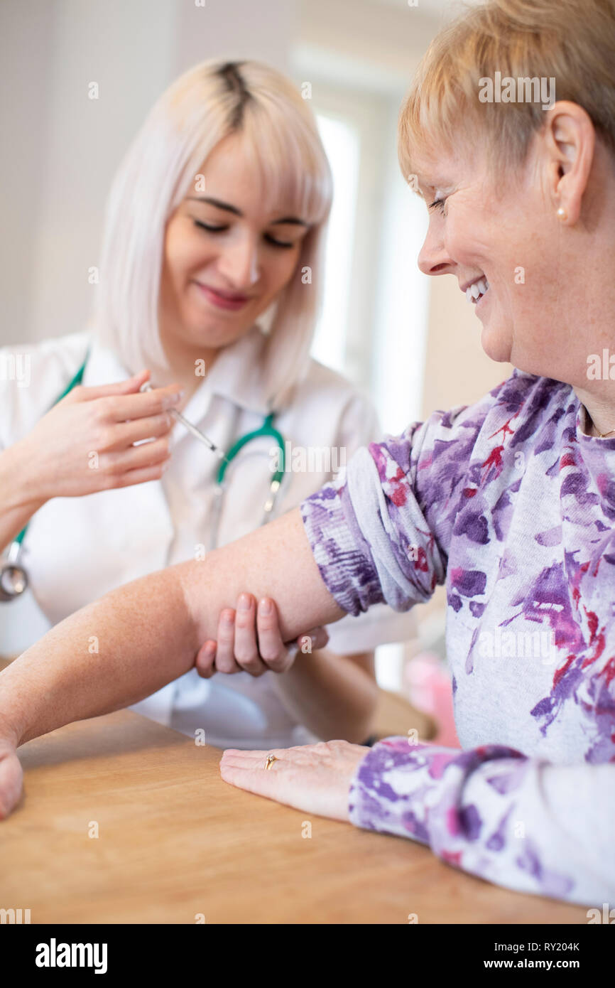 Female Nurse Giving Senior Woman Injection In Arm With Syringe - Stock Image