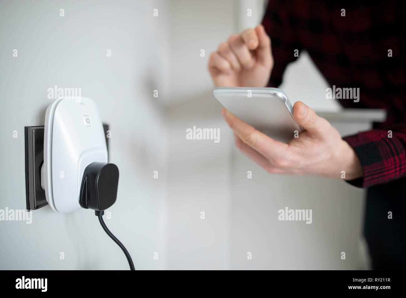Man Controlling Smart Plug Using App On Mobile Phone Stock Photo