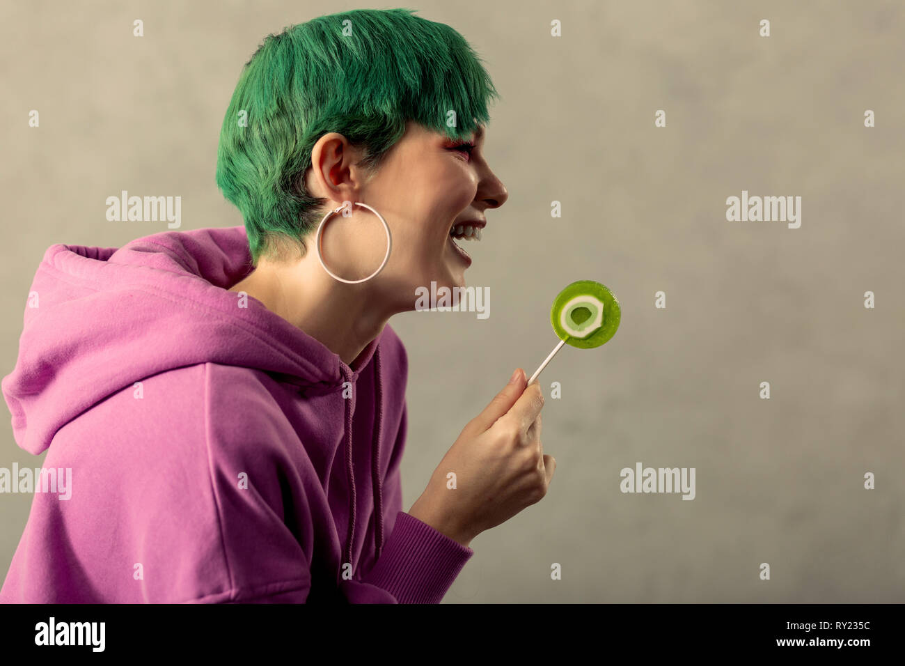Positive green haired woman standing half face - Stock Image