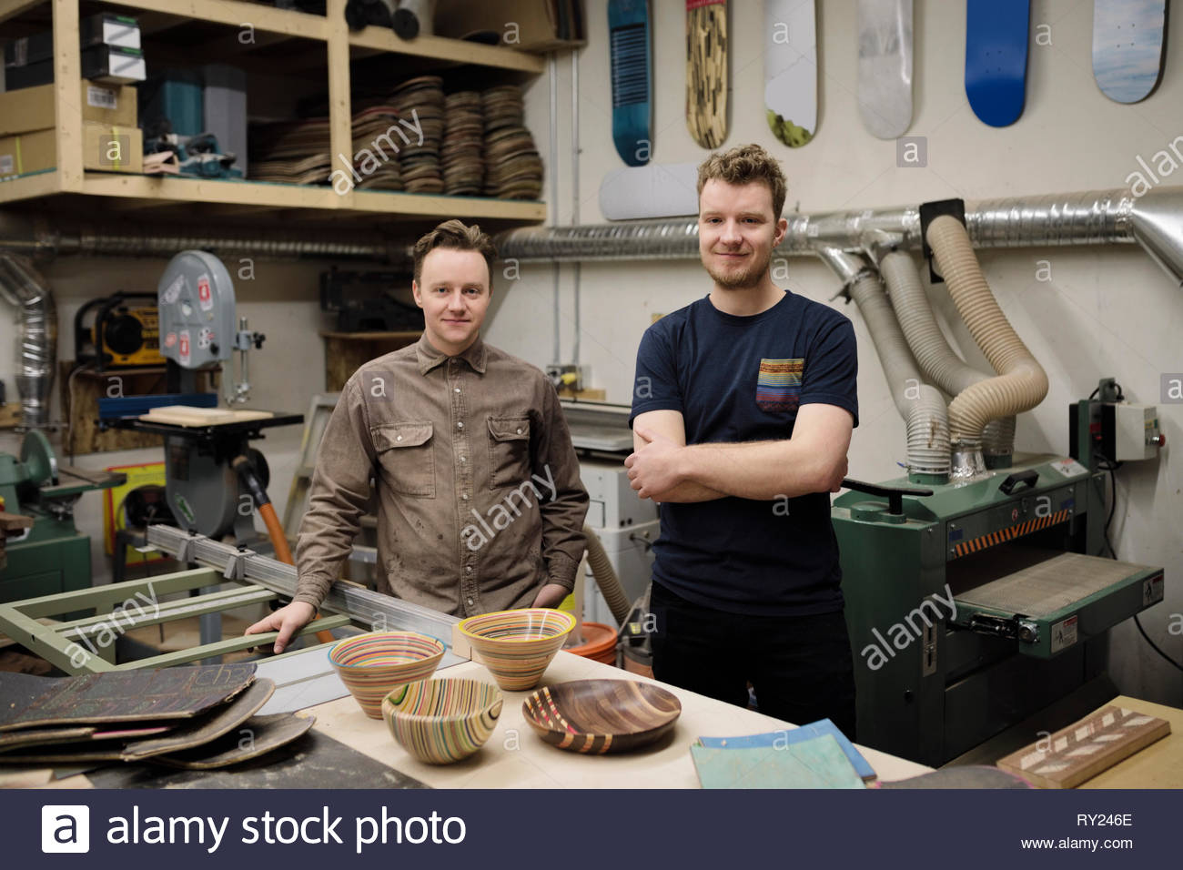 Portrait confident male artists with pottery bowls in workshop - Stock Image