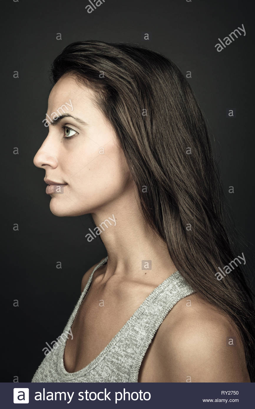 Profile portrait thoughtful beautiful young brunette woman with long hair - Stock Image