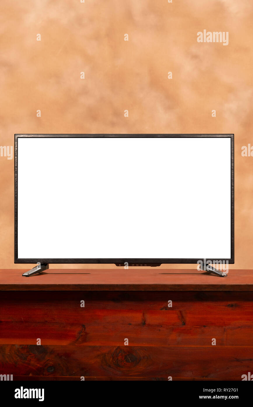 Vertical shot of a blank large screen tv with copy space on table.  Brown muddled background. - Stock Image