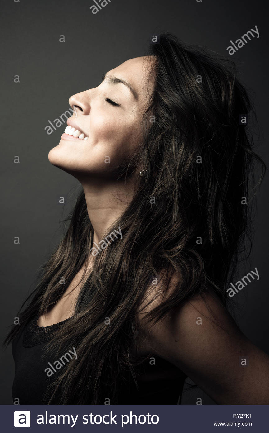 Profile portrait happy beautiful Latina woman smiling with head back - Stock Image
