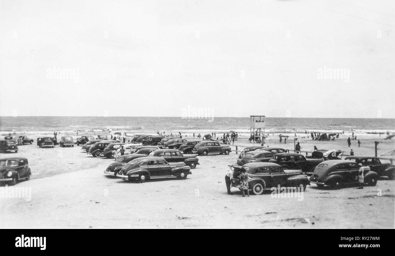 Horizontal black and white photo of people and cars at the beach in the late 1940s. - Stock Image