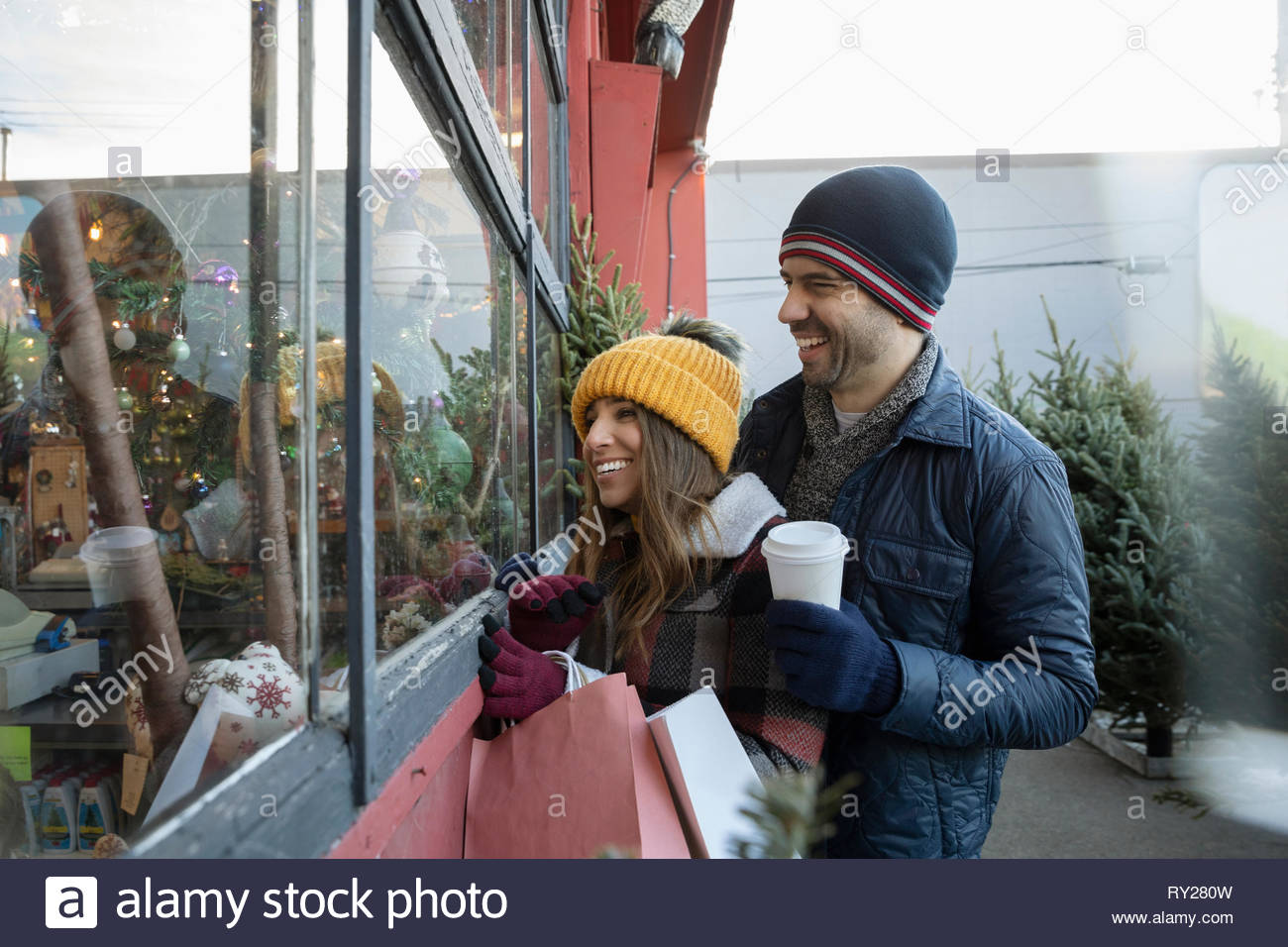 Happy couple with coffee shopping at christmas market - Stock Image