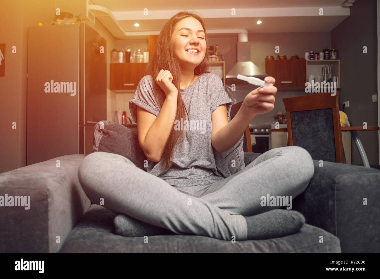 surprised happy young woman and pregnancy test Stock Photo