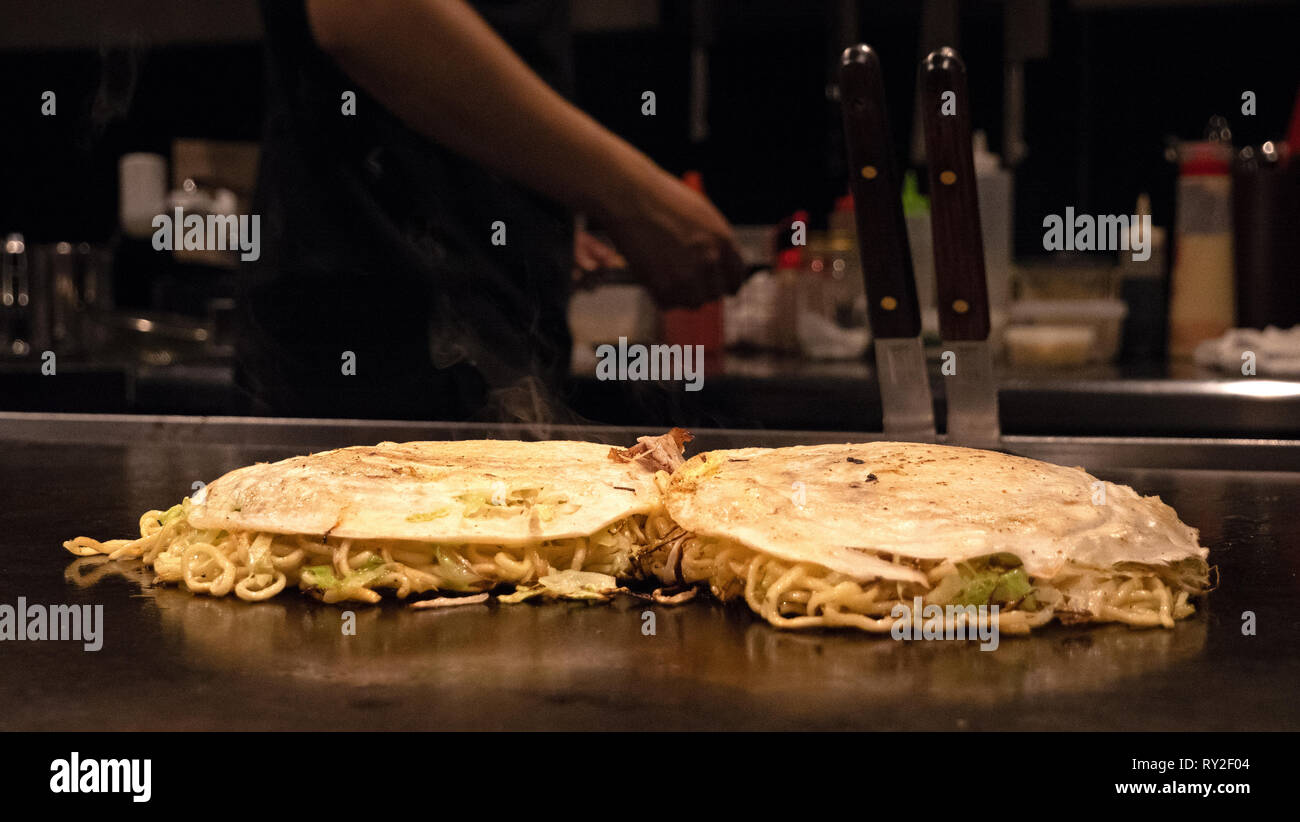 Okonomiyaki  is a Japanese savory pancake containing a variety of ingredients. Toppings and batters tend to vary according to region of Japan. - Stock Image