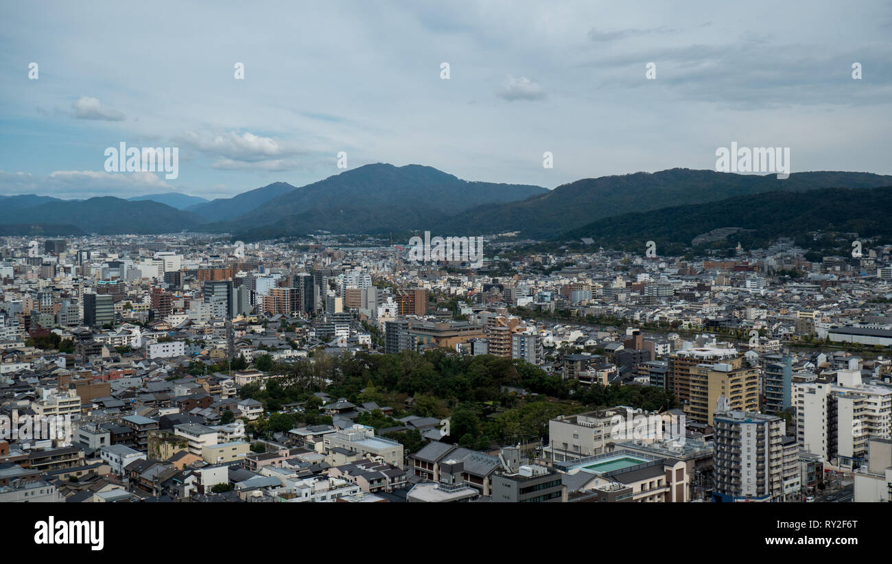 Aerial shots of the city of Kyoto. Skyscrapers and buildings expand out into the distance of the Japanese city as a stormy sky and clouds . - Stock Image