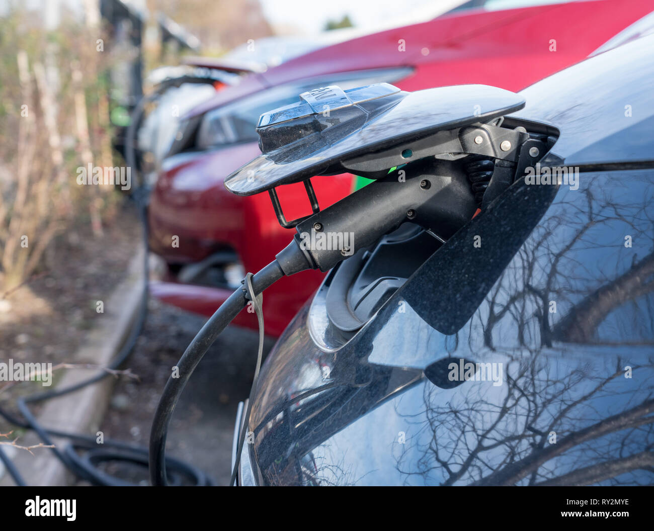 Nissan electric car being recharged in parking lot - Stock Image