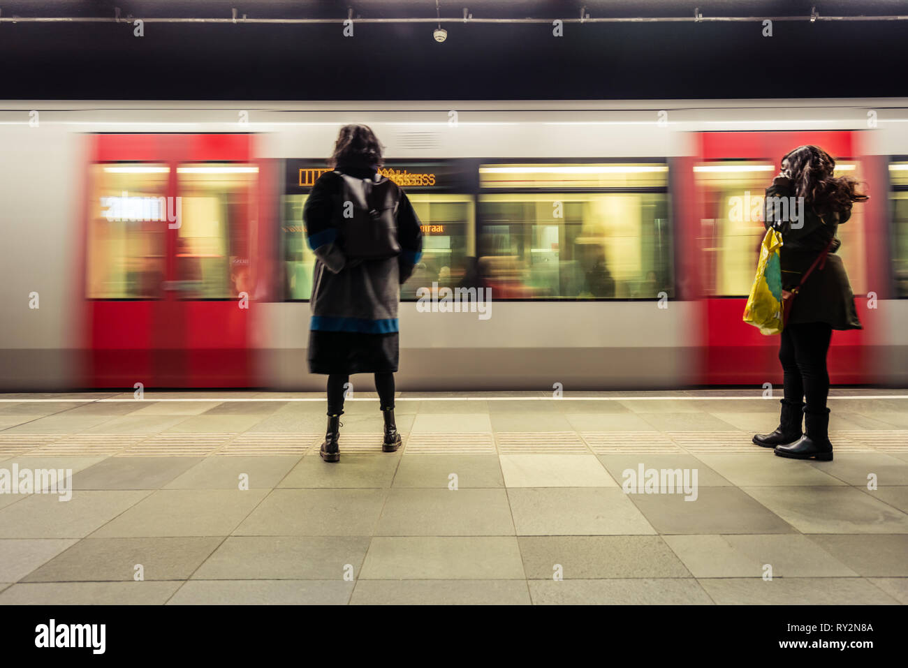 Rear view of woman standing on railroad station platform as metro trein enters the station in Rotterdam The Netherlands - Stock Image