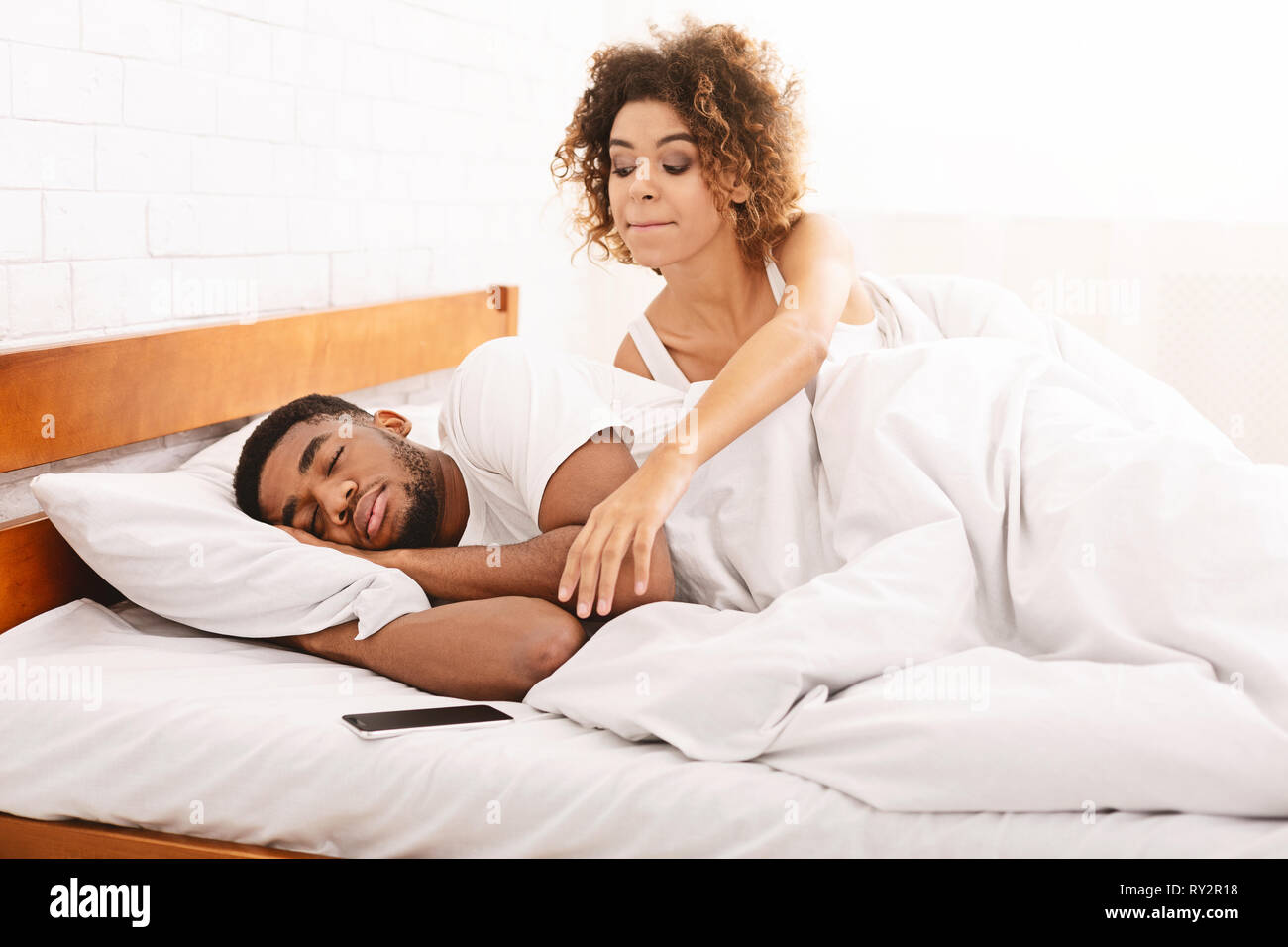Suspicious wife checking her sleeping husband cellphone in bed - Stock Image