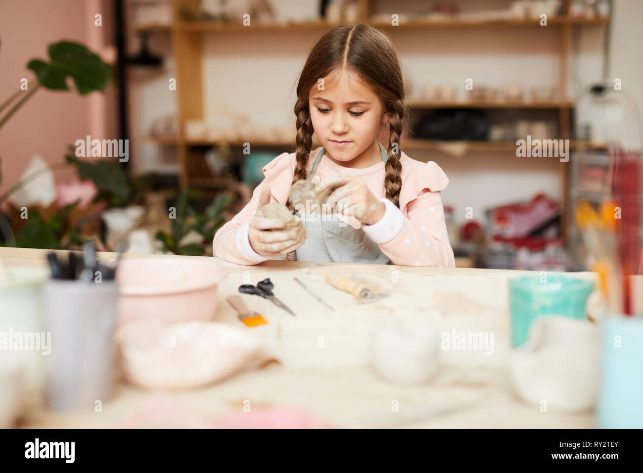Cute Little Girl Shaping Clay - Stock Image