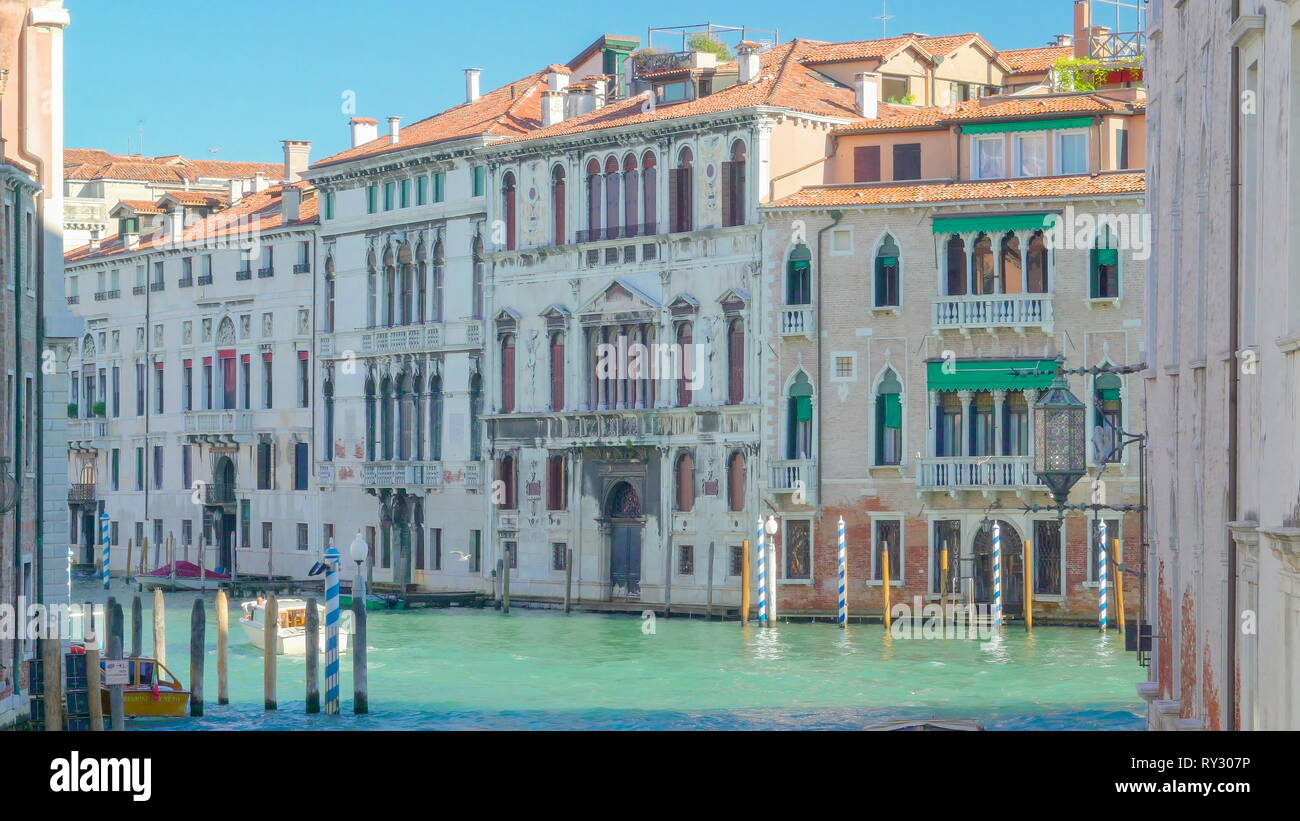 The big buildings lining up on the side of the grand canal with some gondolas touring around in Venice Italy Stock Photo