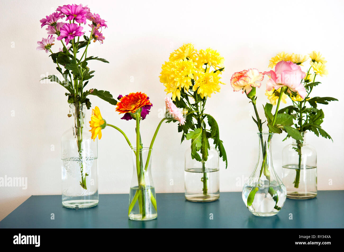 various colorful flowers in differently shaped vases - Stock Image