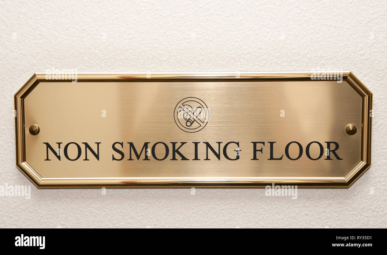 Shiny brass plate restricting smoking on hotel floor - Stock Image
