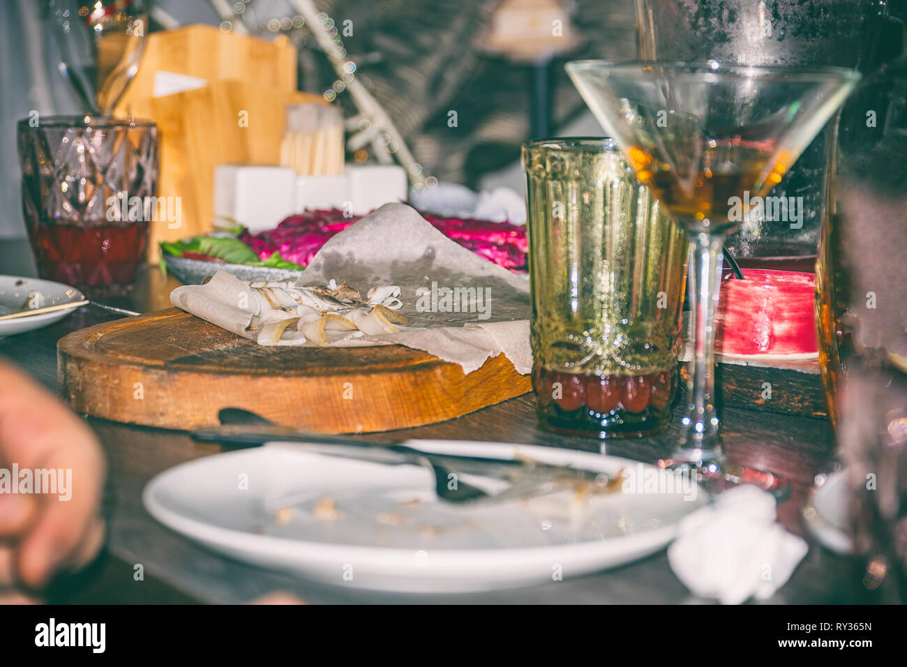 Untidy dirty table after party. Leftover food, empty glasses, wrinkled napkins - Stock Image