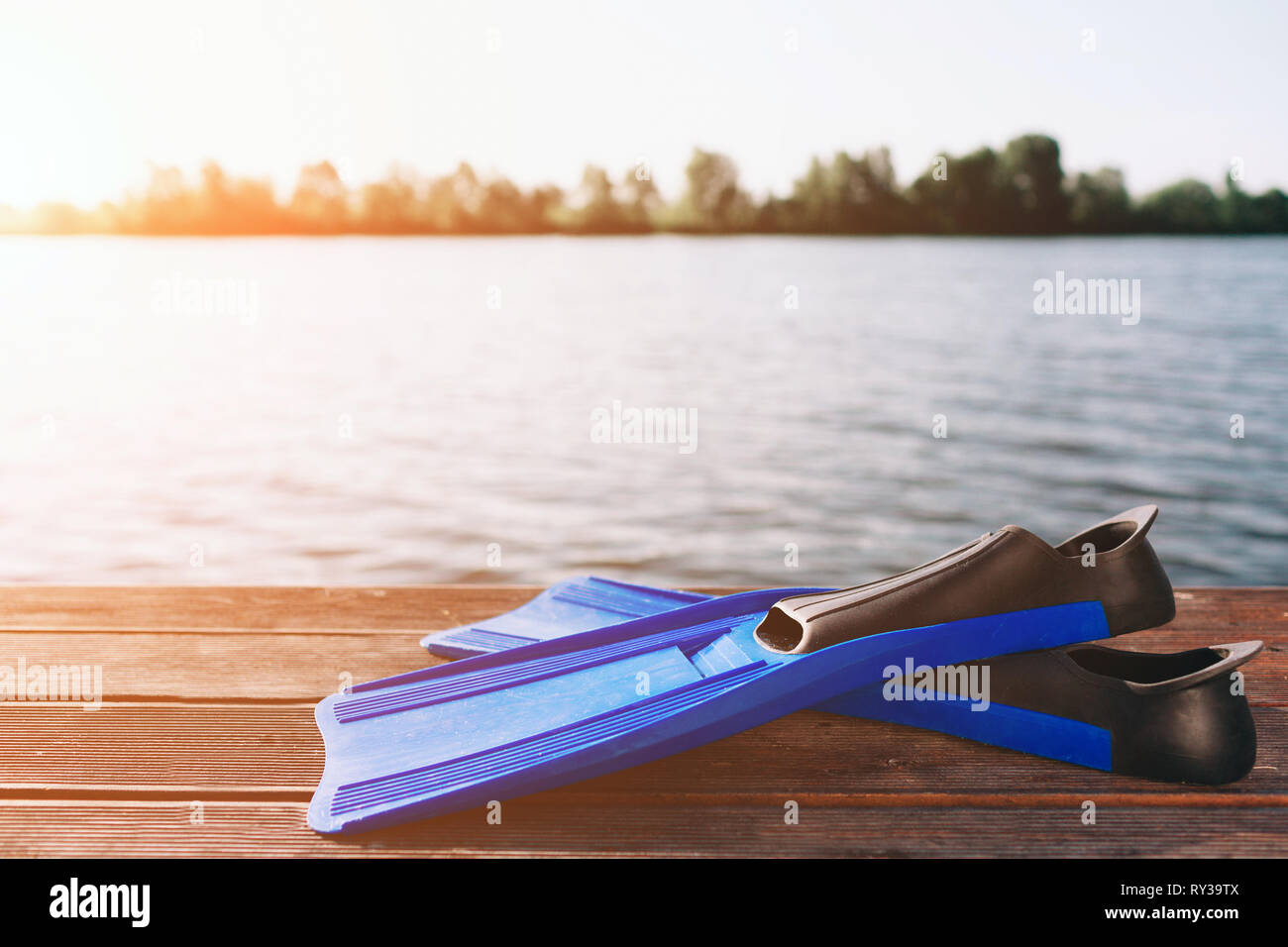Blue fins for swimming on sand beach. Large river or lake. Sun shines. Clear blu sky. - Stock Image