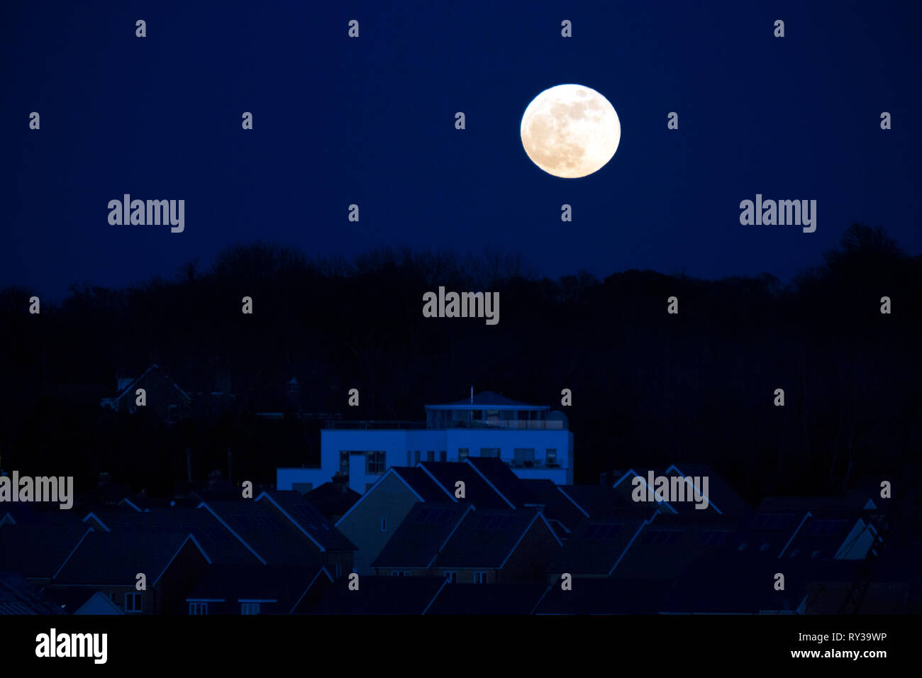Super,moon,rising,above,trees,grand,designs,house,turret,roof,roofs,East,Cowes,Isle of Wight,England, UK, - Stock Image