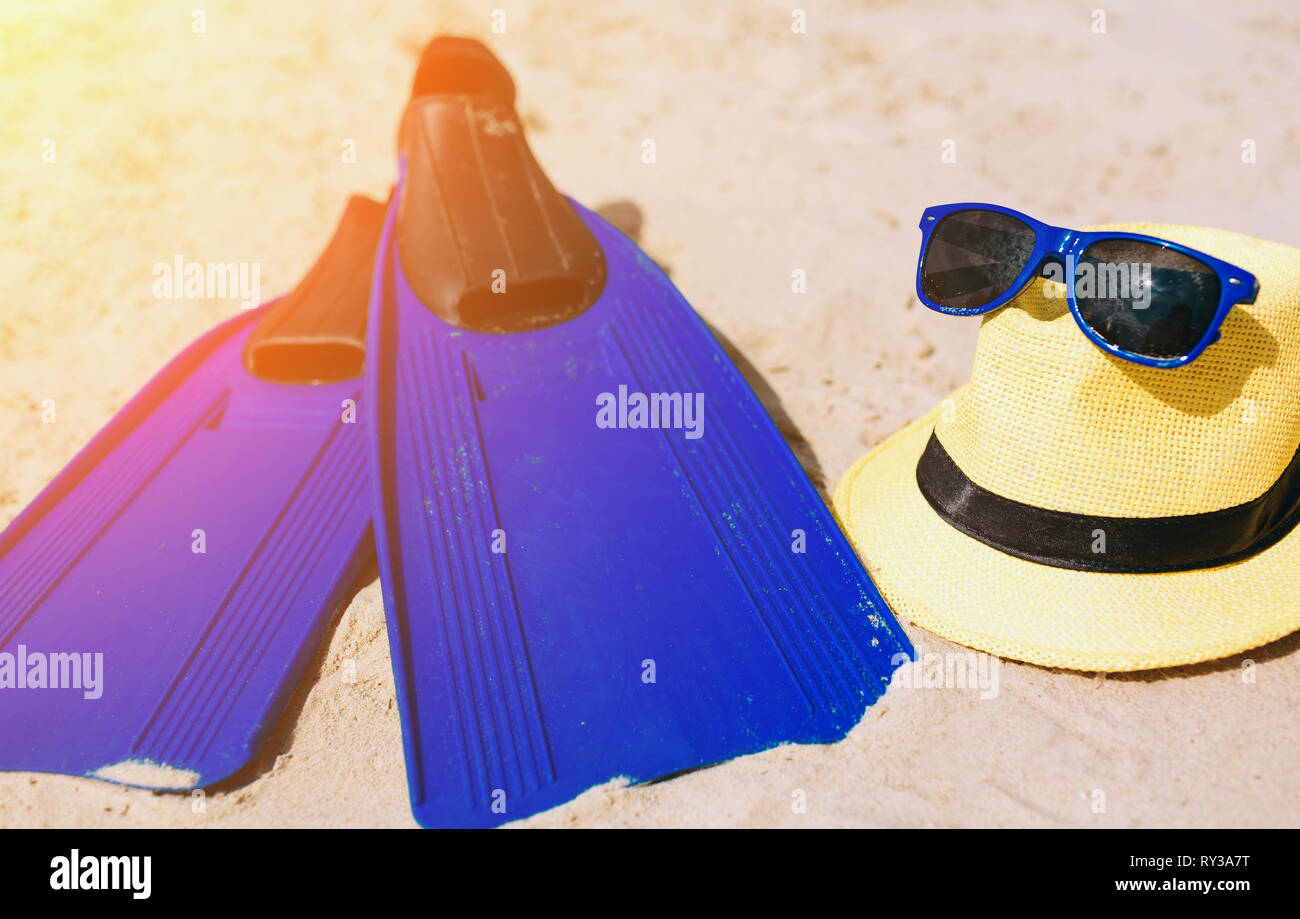 Blue fins hat and sunglasses on the sandy beach. Bright outside. Sun shines. - Stock Image