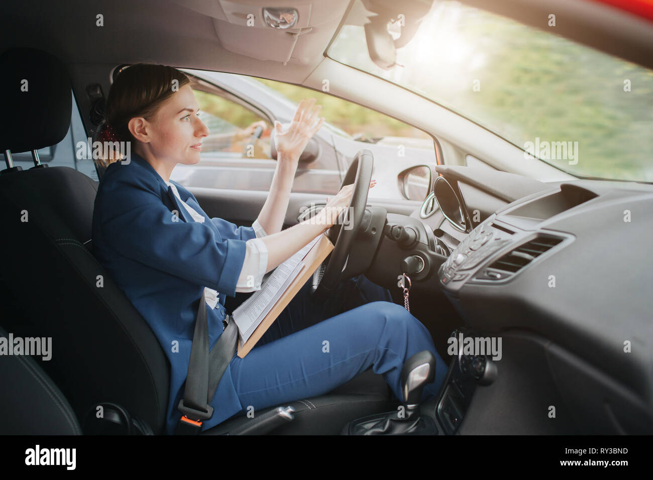 A woman feels stress on the road. Big Traffic jams. Business woman is late for work - Stock Image