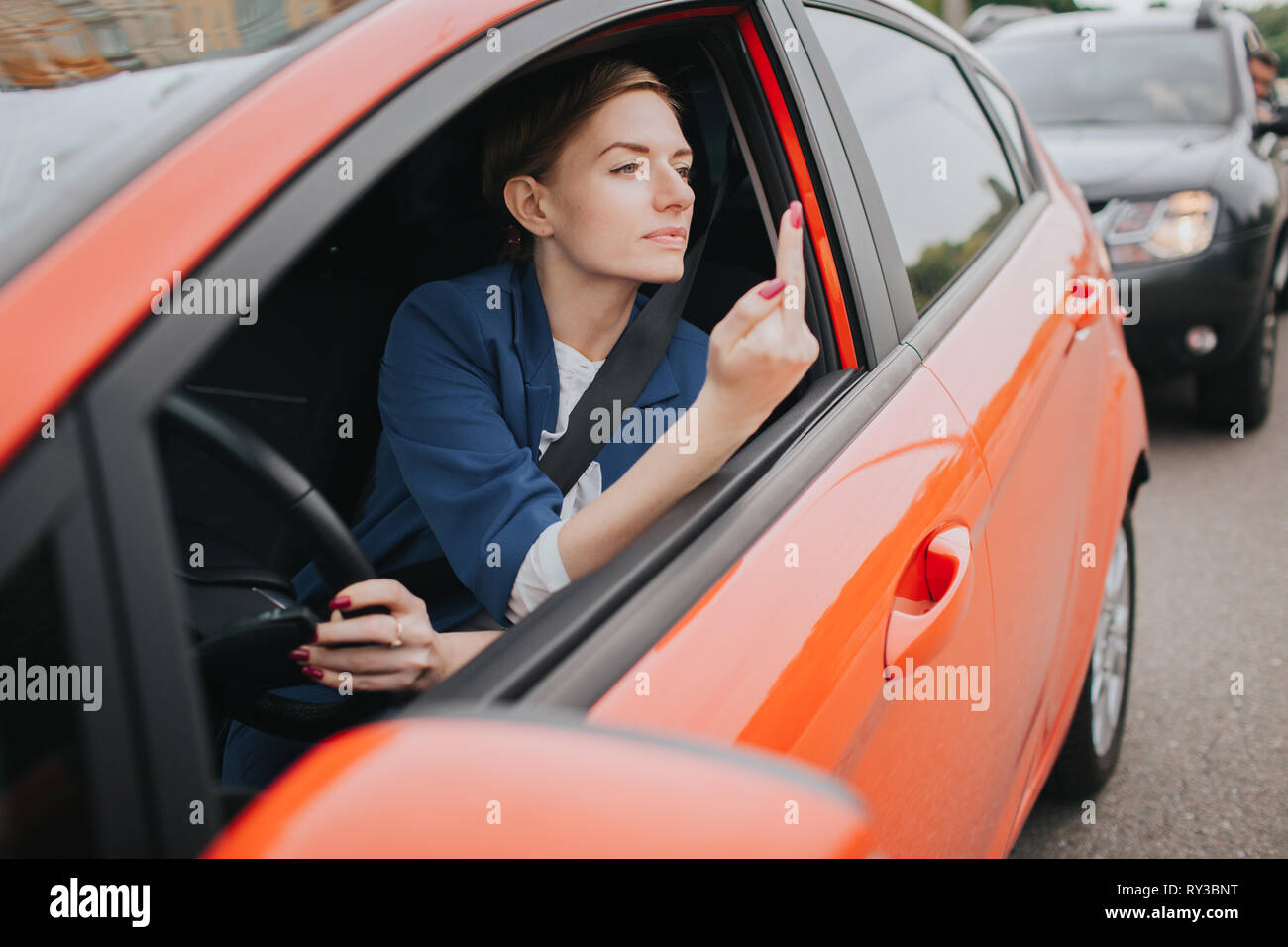 A woman feels stress on the road. Shows the fact in the window. Big Traffic jams. Business woman is late for work - Stock Image