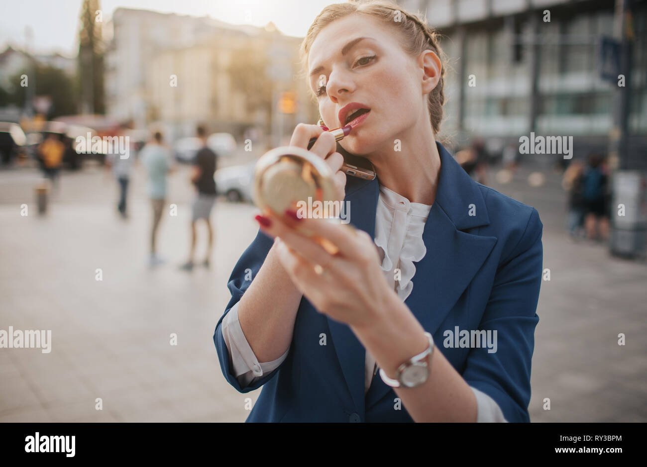 Busy woman is in a hurry, she does not have time, she is going to do make up and to speak on the phone on the go. Businesswoman doing multiple tasks - Stock Image