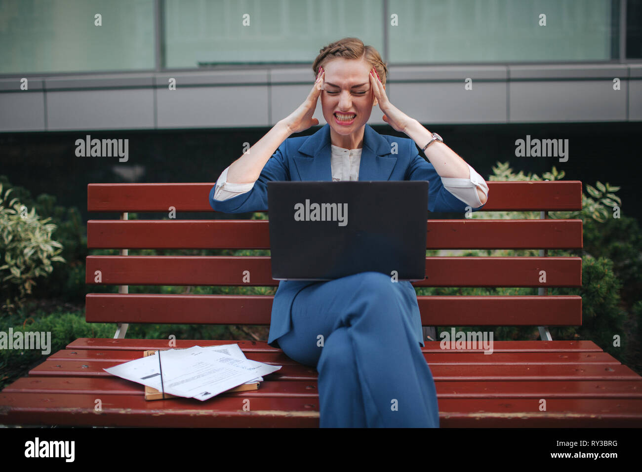 Portrait of stressful businesswoman screaming. She Holds his head with his hands - Stock Image