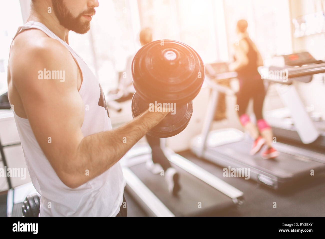 Muscular Bearded man during workout in the gym. Athlete muscular bodybuilder in the gym training biceps with dumbbell. Indoor fitness Stock Photo