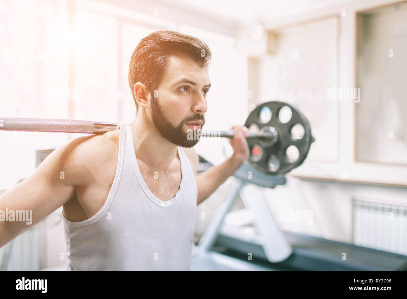 Muscular bearded man during workout in the gym. Bodybuilder doing weight lifting . Close up of young athletic female model trains at the fitness Stock Photo
