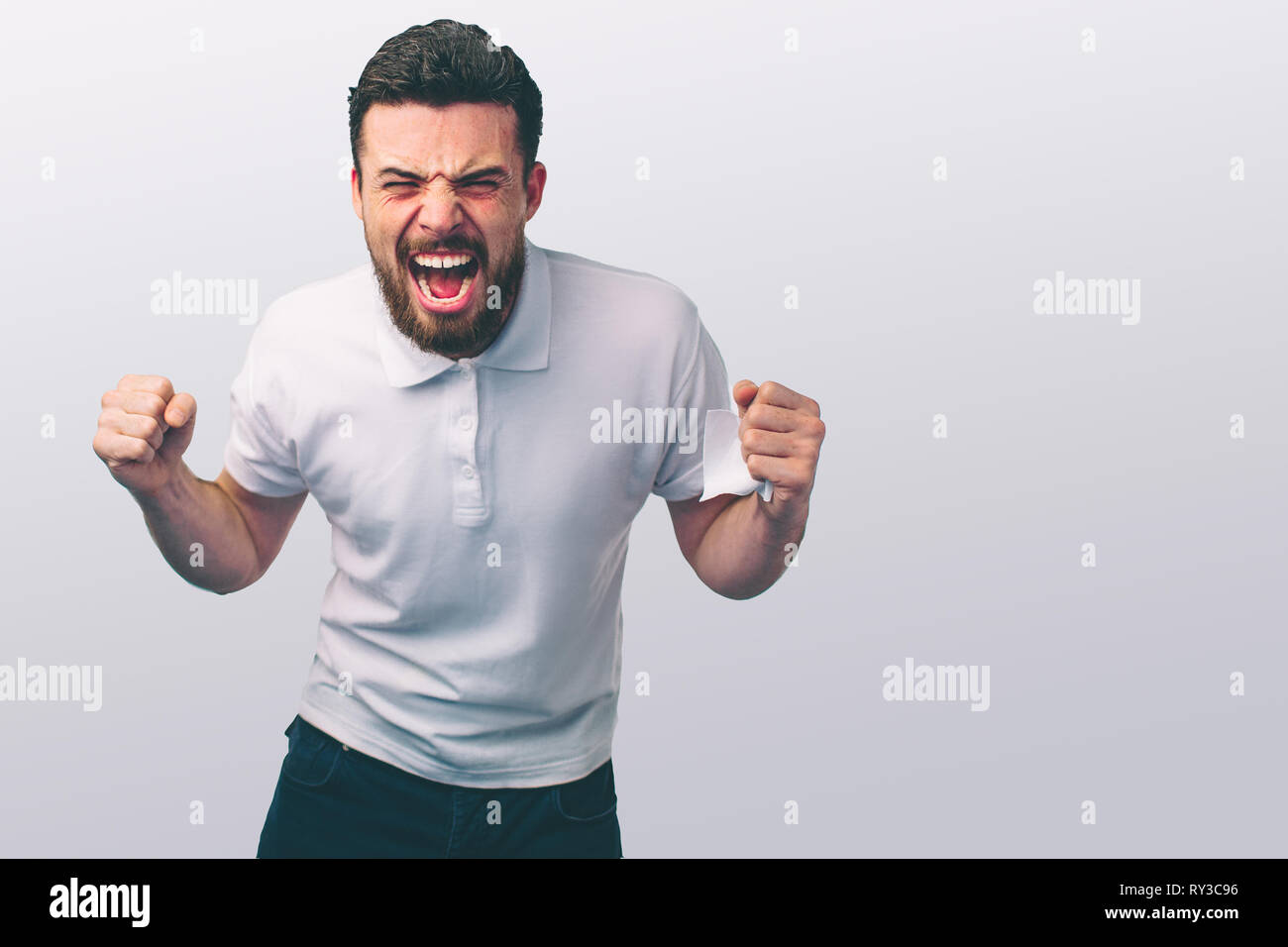 portrait of a angry young man. He is clenches fists and shouts.. The wicked guy beats. - Stock Image