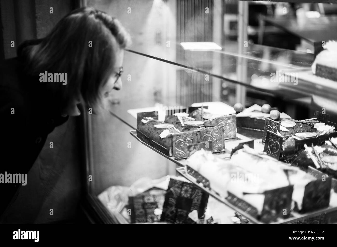 Woman buying sweets a the patisserie bakery store window in French city during Christmas winter holidays  Stock Photo