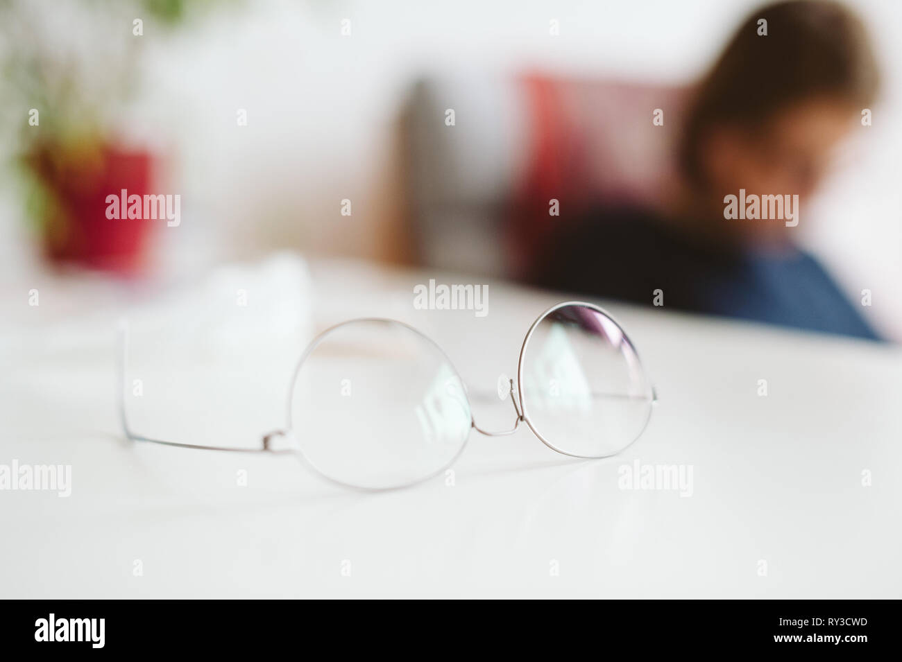 Modern thin-rim titan eyewear glasses spectacles on table with woman defocused silhouette working in the background - Stock Image
